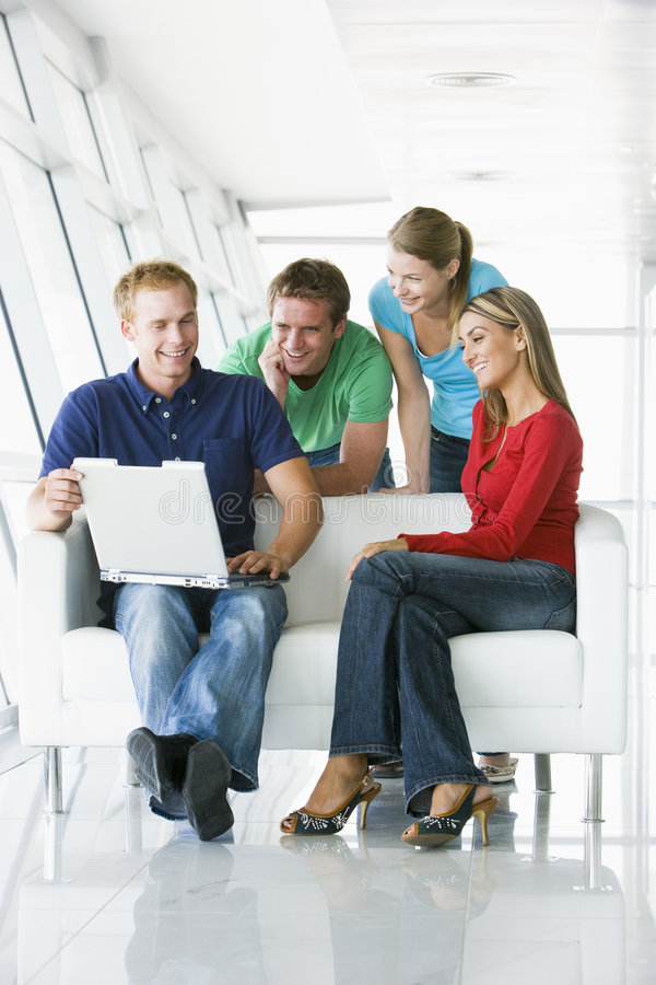 Cuatro personas en el pasillo que mira la sonrisa de la computadora portátil imagen de archivo