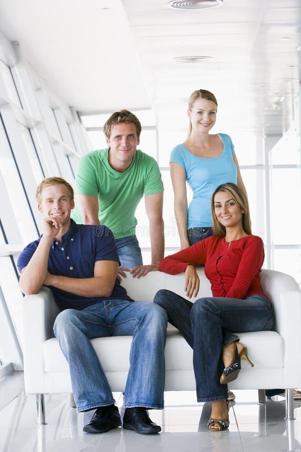 Cuatro personas en la sonrisa del pasillo foto de archivo