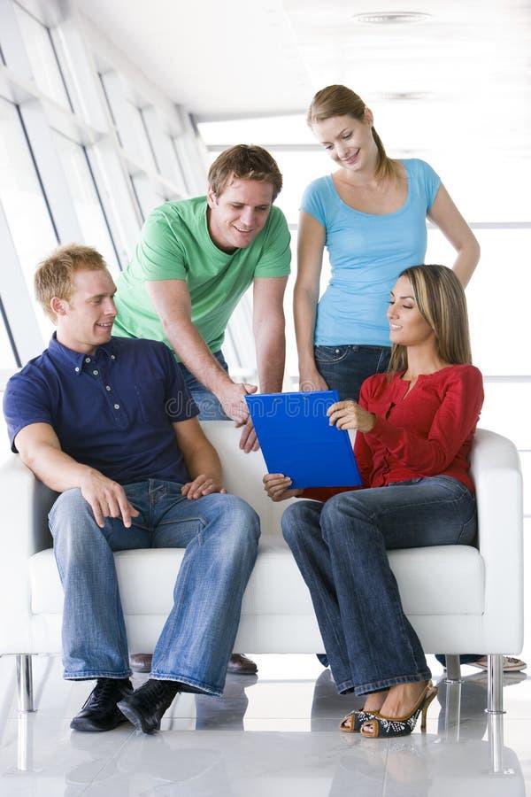 Cuatro personas en pasillo que señalan en la sonrisa del sujetapapeles foto de archivo