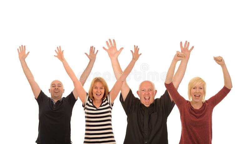 Cuatro personas felices que aumentan los brazos en el aire imagenes de archivo