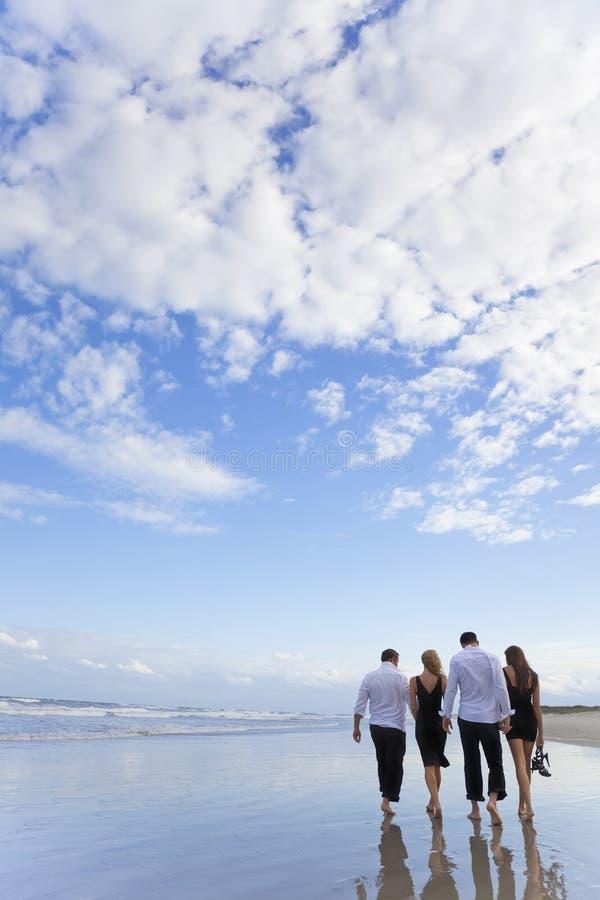 Cuatro personas jovenes, dos pares, recorriendo en una playa imagen de archivo libre de regalías
