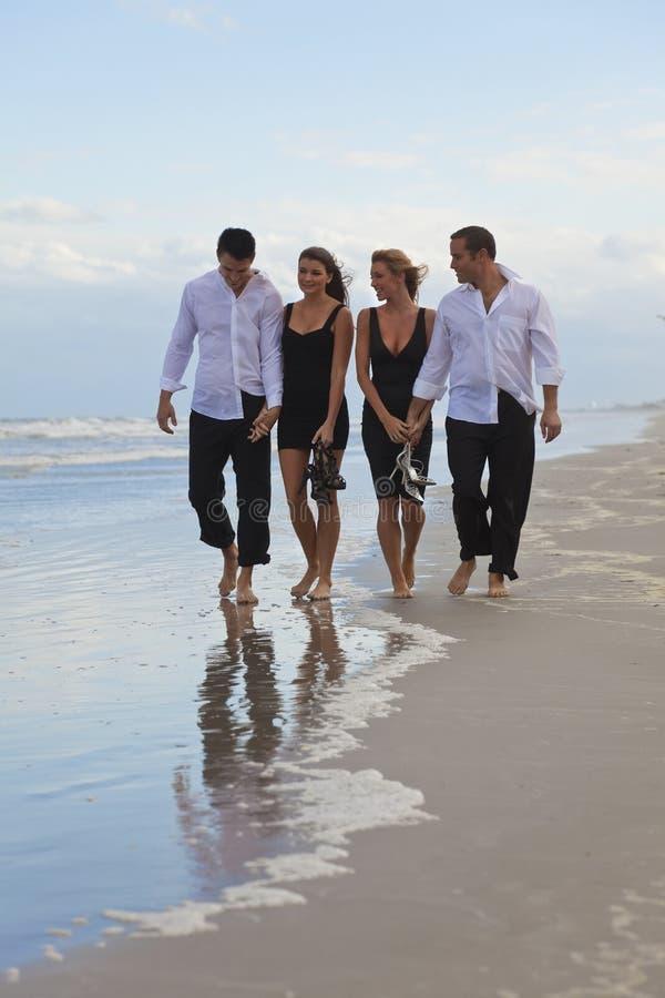 Cuatro personas jovenes, dos pares, recorriendo en una playa imagenes de archivo