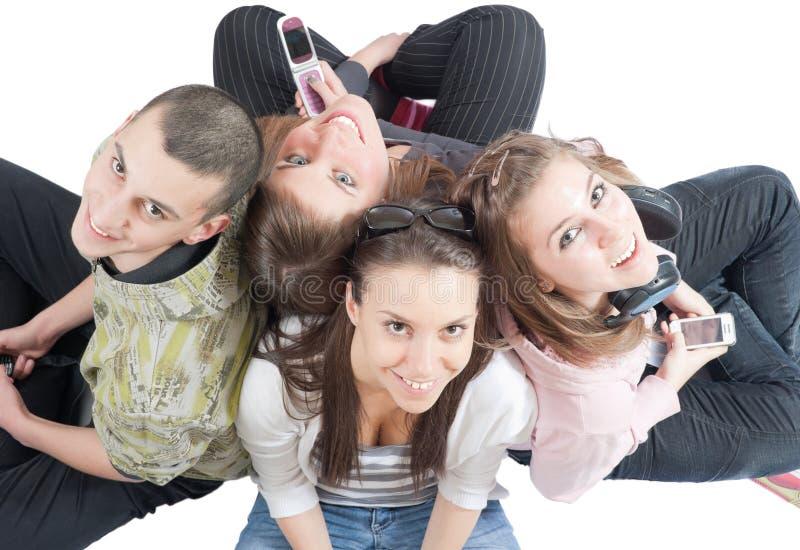 Cuatro personas jovenes en el suelo blanco fotos de archivo libres de regalías