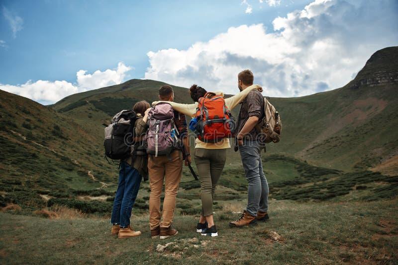 Cuatro personas que se colocan cerca de uno a y que disfrutan de la visión imágenes de archivo libres de regalías