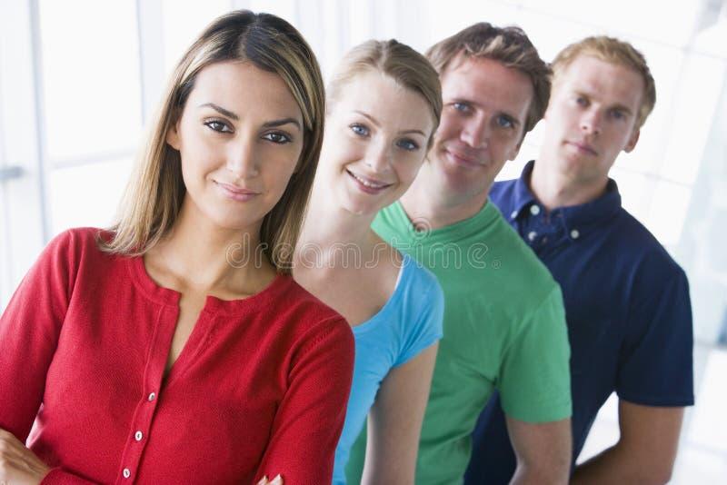 Cuatro personas que se colocan en la sonrisa del pasillo imagen de archivo libre de regalías