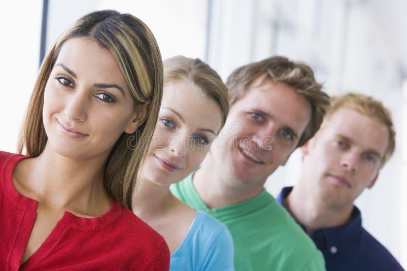 Cuatro personas que se colocan en la sonrisa del pasillo imagenes de archivo
