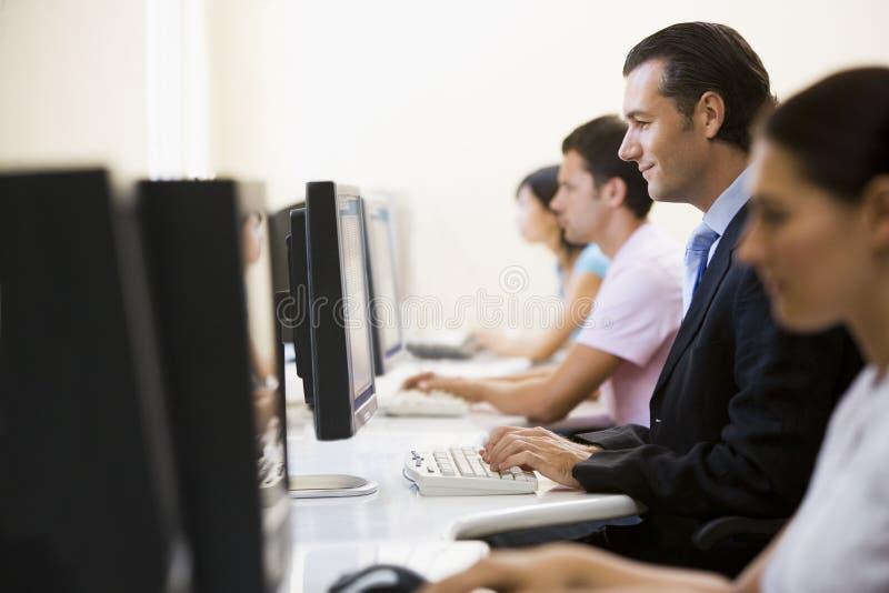 Cuatro personas que se sientan en pulsar de la sala de ordenadores imagen de archivo libre de regalías