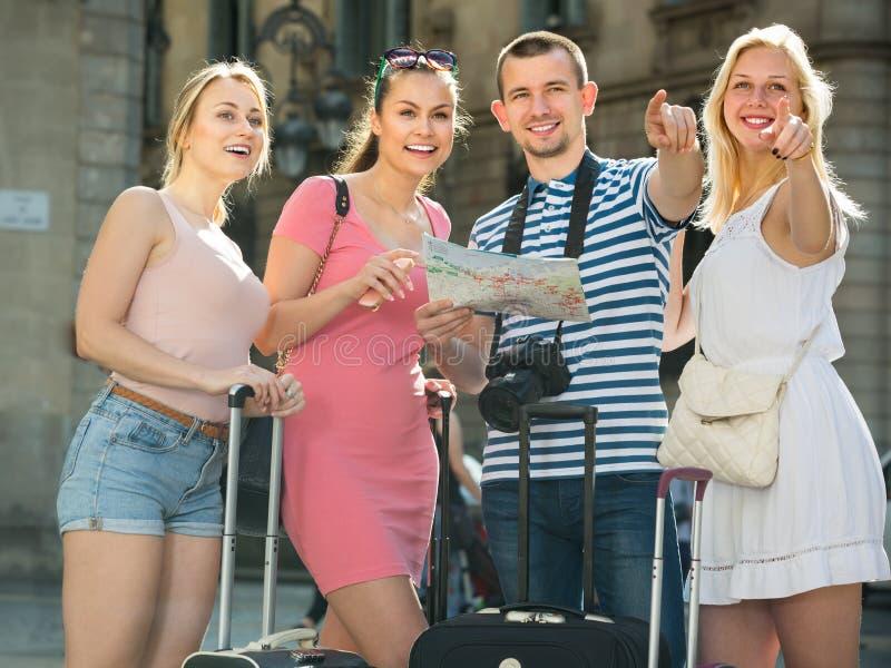 Cuatro personas que viajan felices que usan el mapa de papel foto de archivo libre de regalías