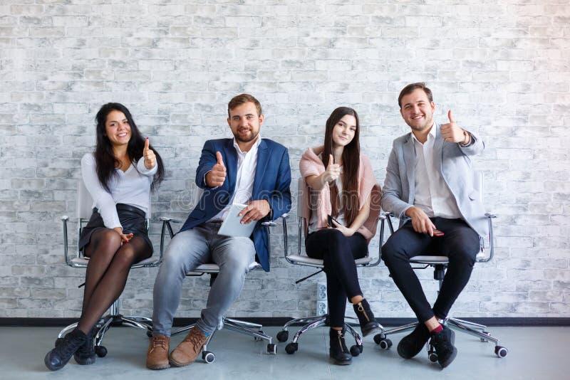 Cuatro personas se están sentando y el mostrar los pulgares-para arriba gesticula en su mano y sonrisa extendidas fotografía de archivo