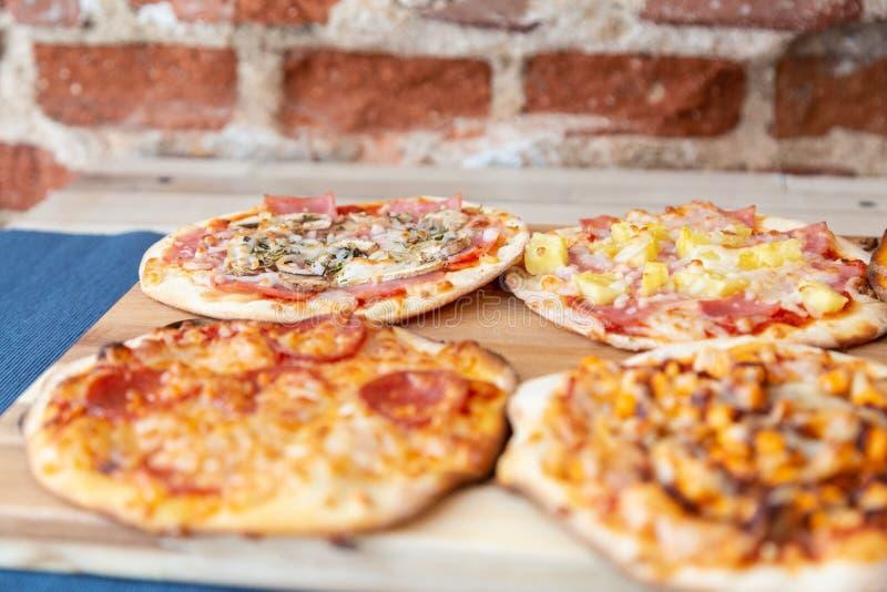 Cuatro pizzas en un tablero de madera, fresco fuera del horno imagen de archivo