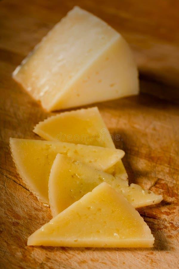 Cuatro rebanadas y una cuña del queso de Manchego imagen de archivo