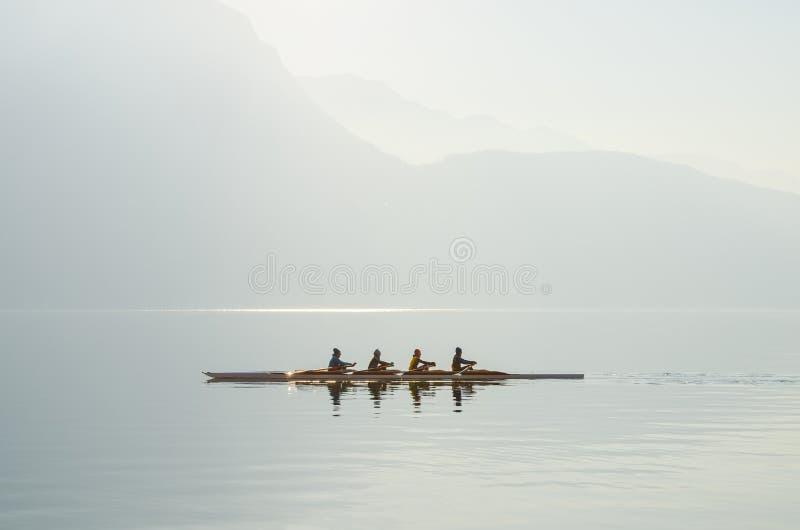 Cuatro remeros en el barco que flota en mañana soleada en el fondo de montañas en el lago de Lugano imágenes de archivo libres de regalías