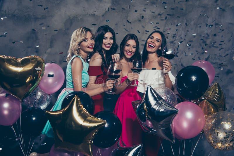 Cuatro señoras alegres alegres magníficas atractivas de la elegancia fascinadora preciosa magnífica atractiva que gozan del vino  fotografía de archivo