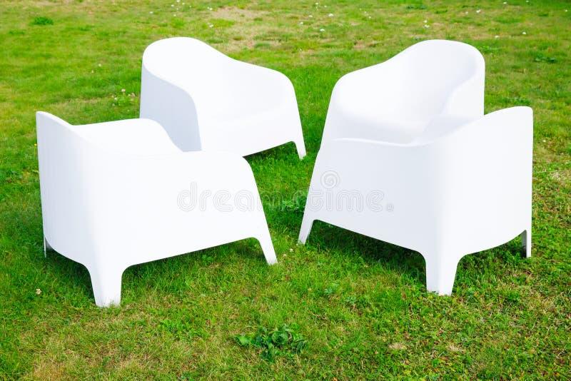 Cuatro sillas pl sticas blancas modernas se colocan en for Sillas blancas modernas