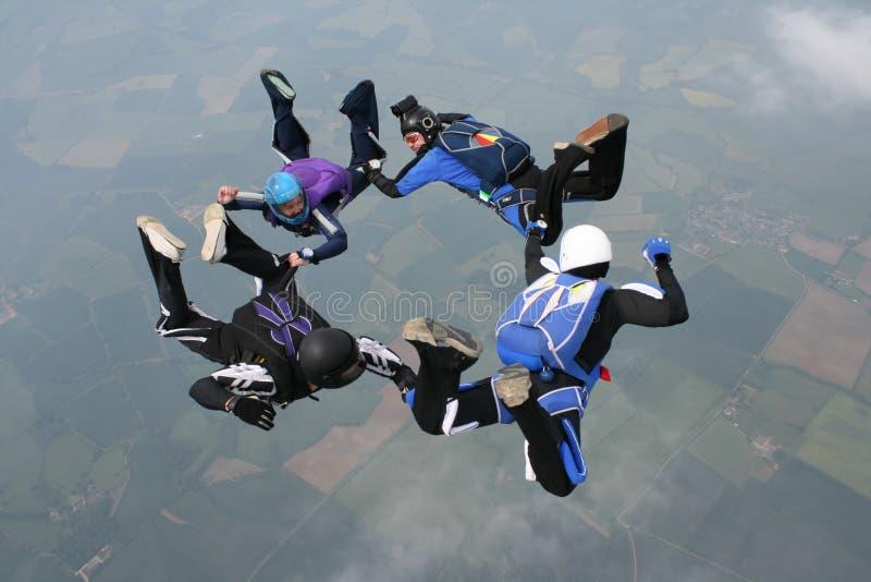 Cuatro skydivers en la caída libre que forma un círculo imagen de archivo libre de regalías