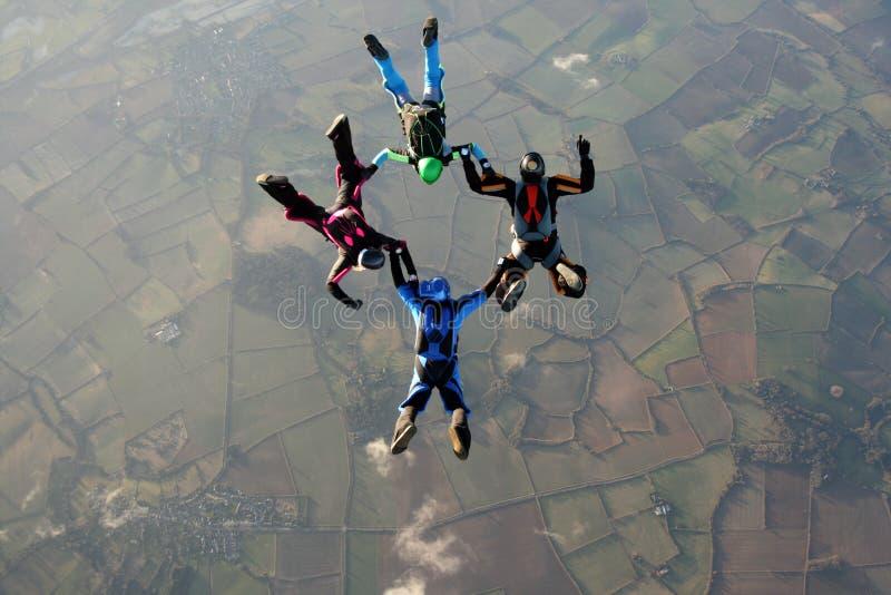 Cuatro skydivers que hacen formaciones imagenes de archivo