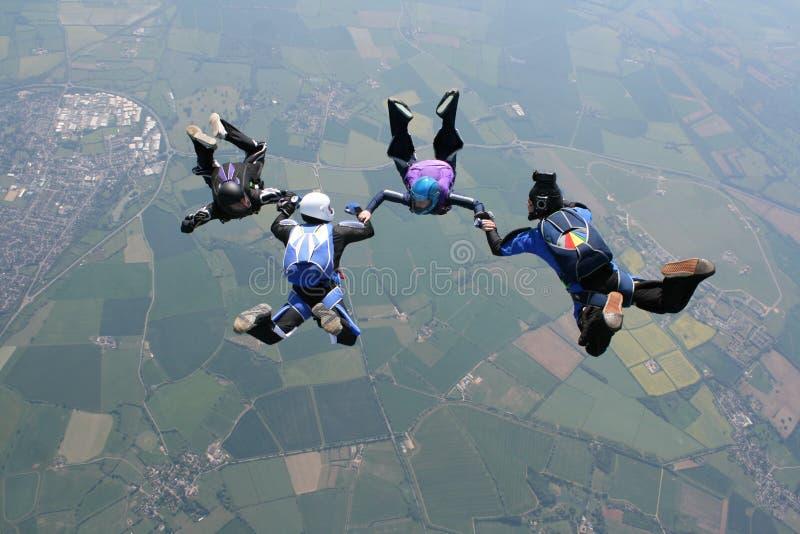 Cuatro skydivers que llevan a cabo las manos foto de archivo libre de regalías