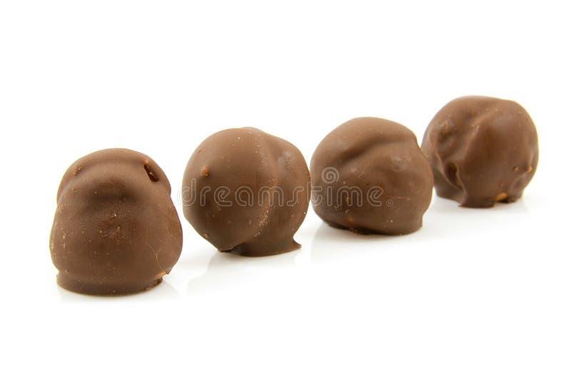 Cuatro soplos poner crema del chocolate marrón en una fila fotografía de archivo