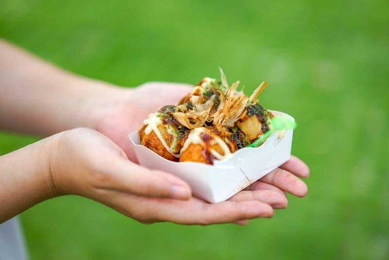 Cuatro Takoyaki, bola de carne japonesa local del pulpo en la mano con el fondo grean de la falta de definici?n, preparado imagen de archivo libre de regalías