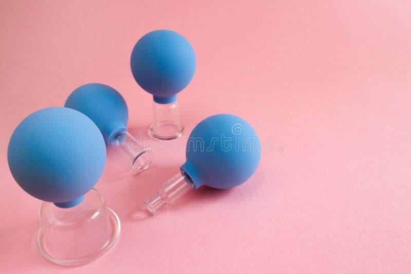 Cuatro tarros cosméticos azules del vacío para el masaje del cuerpo y de cara de diversos tamaños hechos del vidrio y del caucho  imagenes de archivo
