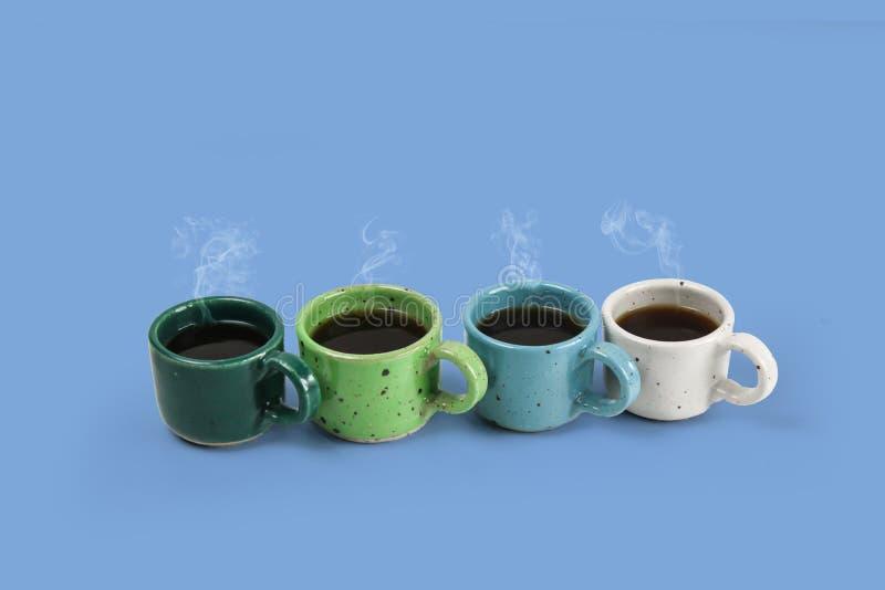 Cuatro tazas coloridas con café fresco en fondo de los colores, imagenes de archivo