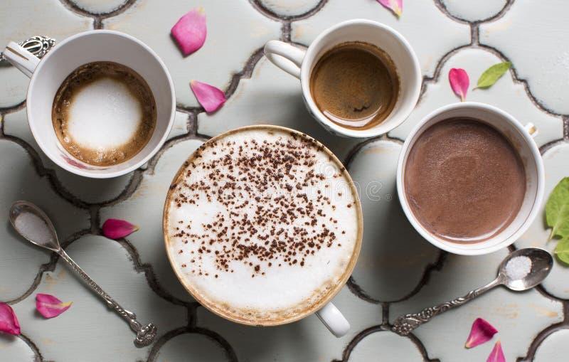 Cuatro tazas de café y de chocolate aromáticos calientes Chocolate caliente, café express, macchiato del café express y latte bel fotografía de archivo libre de regalías