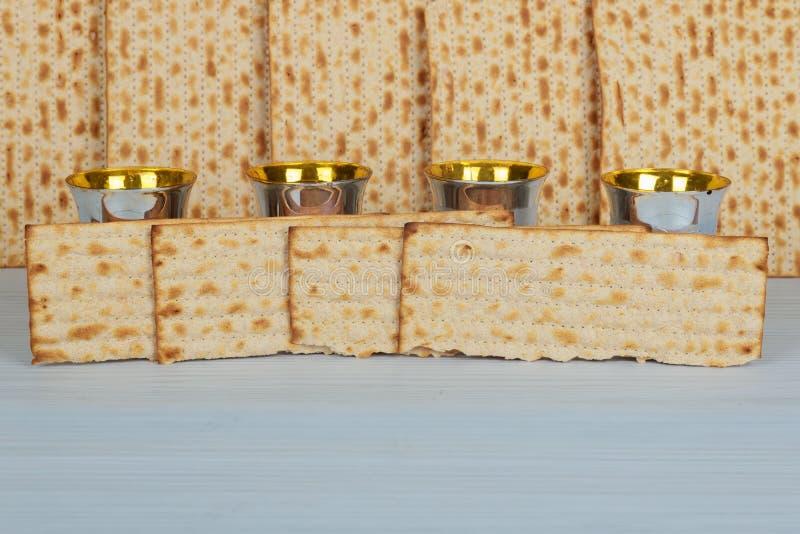 Cuatro tazas de cierre del vino de la pascua judía encima de la textura del matzah en fondo fotografía de archivo libre de regalías