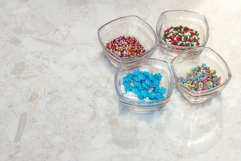 Cuatro tazas de cristal transparentes con las decoraciones para la confitería y hornada en el fondo de mármol foto de archivo