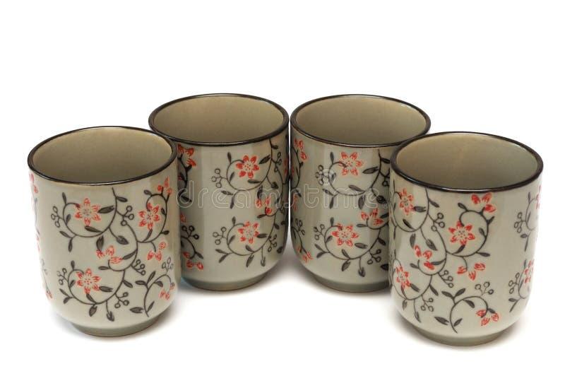 Cuatro tazas de la arcilla con diseño floral rojo del grabado foto de archivo libre de regalías