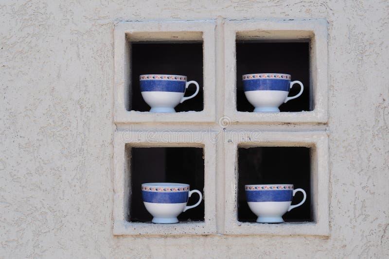 Cuatro tazas de la porcelana en la ventana imagen de archivo