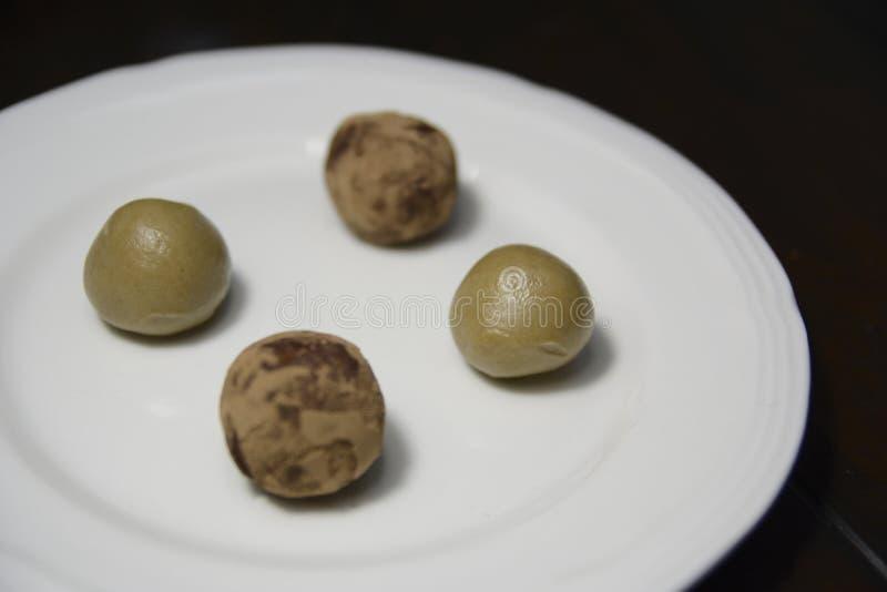 Cuatro trufas libres del gluten en una placa blanca fotos de archivo