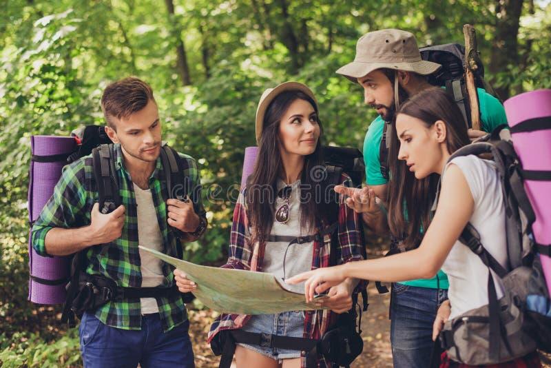 Cuatro turistas consiguieron perdidos en el bosque, sosteniendo el mapa, intentando a la aleta fotografía de archivo