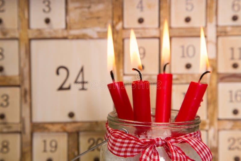 Cuatro velas ardientes rojas del advenimiento con el calendario fotos de archivo