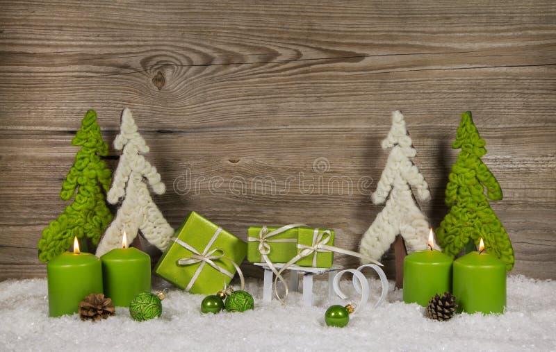 Cuatro velas ardientes verdes de la Navidad con los presentes y los árboles encendido imagenes de archivo