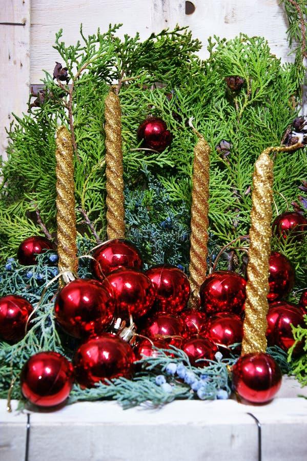Cuatro velas de oro y bolas rojas de la Navidad imagenes de archivo