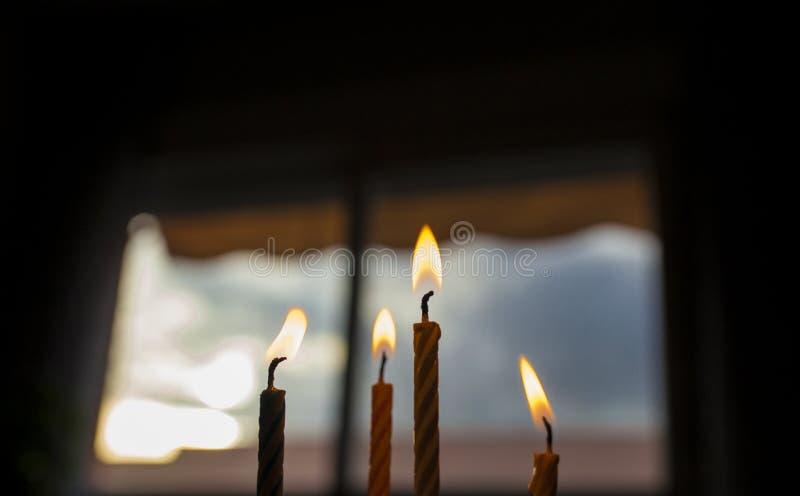 Cuatro velas del cumpleaños encima de una torta sobre el cielo azul de la ventana oscura foto de archivo libre de regalías