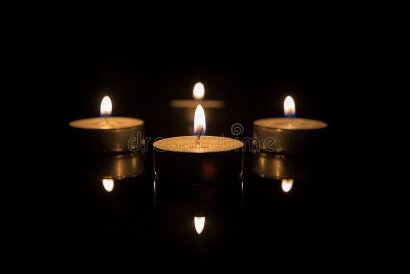 Cuatro velas del té con la reflexión en negro foto de archivo libre de regalías