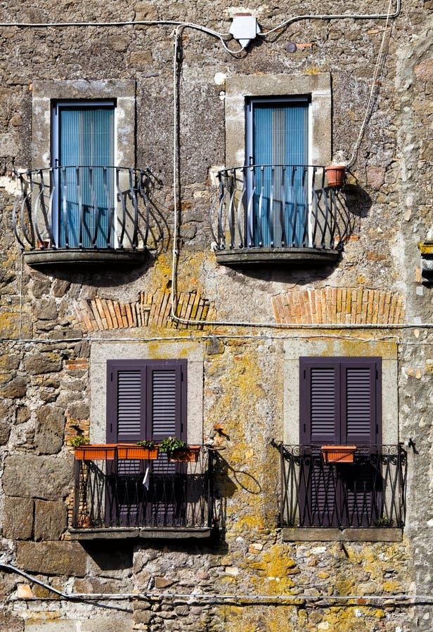 Cuatro ventanas coloreadas con el balcón Viejo estilo italiano del vintage fotos de archivo