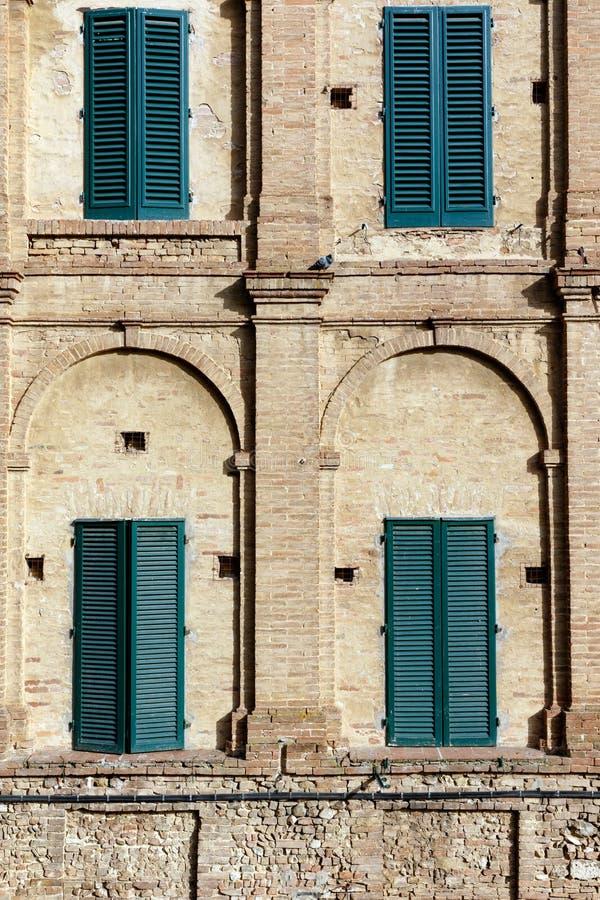 Cuatro ventanas shuttered en una pared de ladrillo geom?trica imagen de archivo libre de regalías