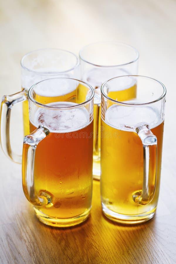 Cuatro vidrios de cerveza fresca de la cerveza dorada en la tabla fotografía de archivo