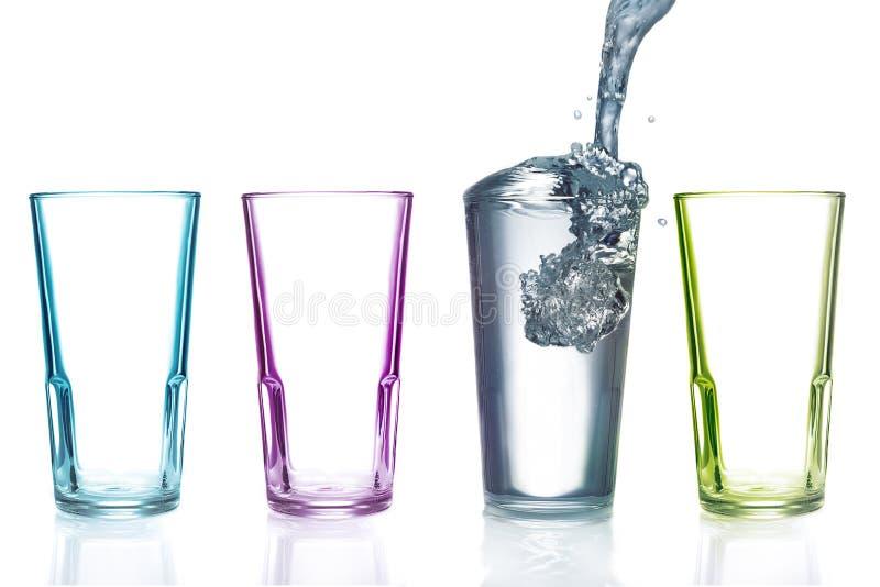 Cuatro vidrios de consumición coloridos, uno con agua fotografía de archivo libre de regalías