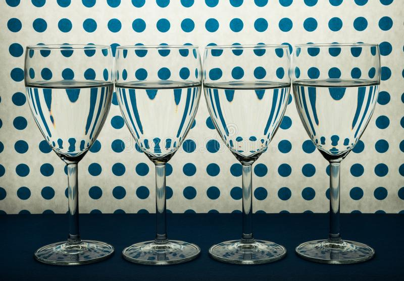 Cuatro vidrios transparentes para el vino que se coloca en línea y el fondo blanco con los puntos azules imagen de archivo libre de regalías