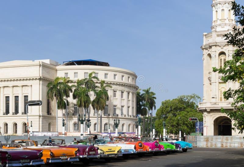 Cuba che molte automobili classiche hanno parcheggiato in serie a Avana con la vista del Campidoglio fotografia stock libera da diritti