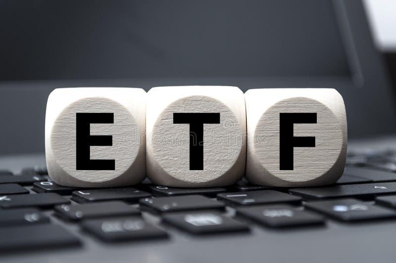 Cuba dados e calculadora com ETF no teclado de madeira do fundo e do portátil foto de stock