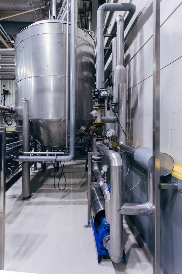 Cuba de acero inoxidable industrial con la tubería en cervecería moderna fotos de archivo