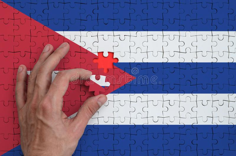 Cuba flag is depicted on a puzzle, which the man`s hand completes to fold stock photos
