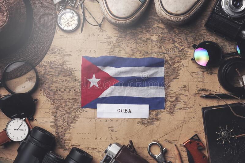 Cuba Flag Between Traveler`s Accessories on Old Vintage Map. Overhead Shot.  royalty free stock photography