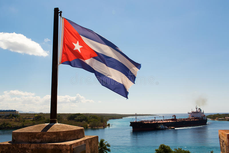Cuba flag waving on the wind with a big boat in background stock photos