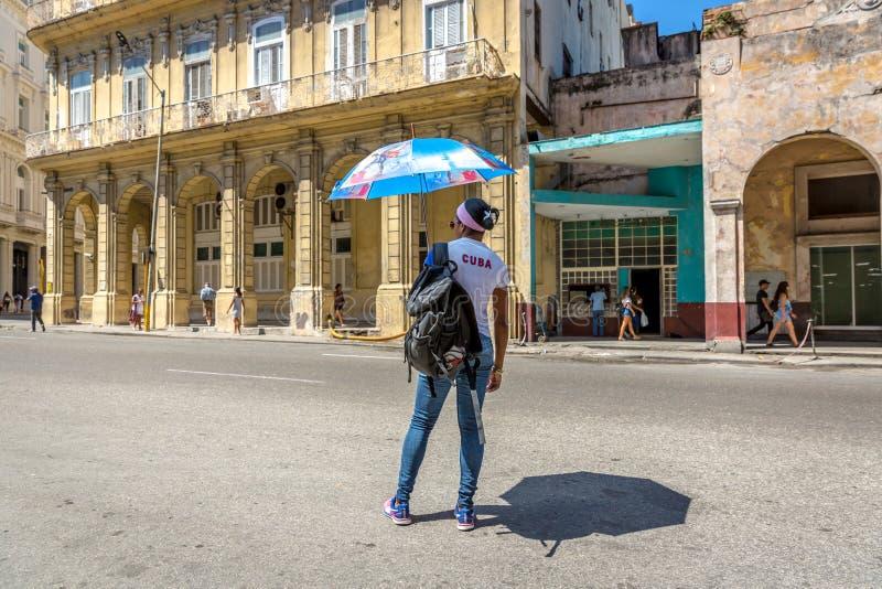 Cuba, Havana - breng 9de 2018 in de war - Eenzame vrouw die op een auto in een straat die van Havana wachten, een t-shirt van Cub stock afbeeldingen