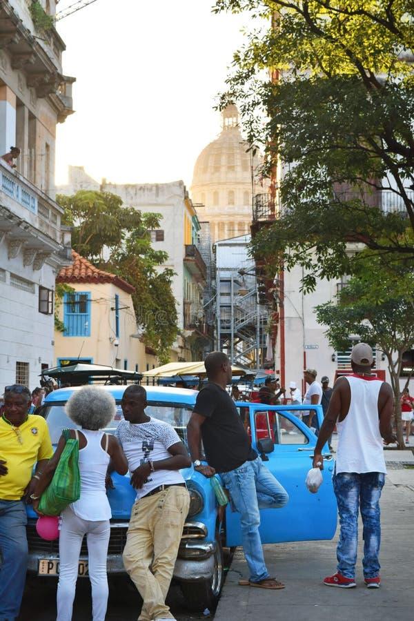 Cuba, Havana - 17 de fevereiro de 2018: um dia típico em uma das ruas de Havana, povos que conversam e que relaxam fotografia de stock